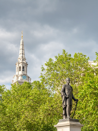 sir: Major General Sir Henry Havelock statue at Trafalgar square with Saint Martin-in-the-Field church clock tower behind, under cloudy sky