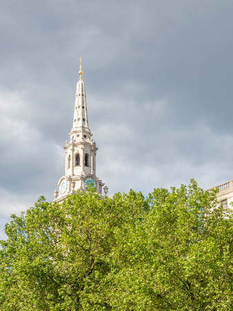 Clock tower of Saint Martin-in-the-Fields church with green tree foreground under cloudy sky in London, England Stock Photo