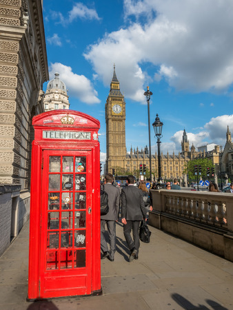 LONDON - MAY 24: Two of London symbols, Big Ben and red phone booth, under cloudy blue sky in London, England, was taken on May 24, 2016.