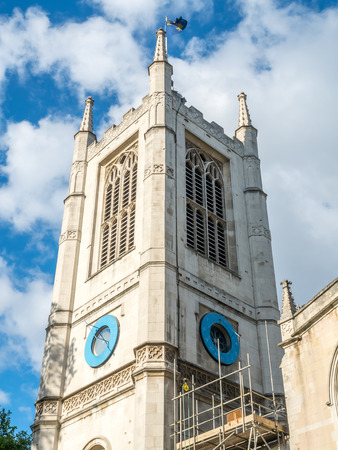 Tower of Saint Margarets church in Westminster Abbey area under cloudy blue sky in London, England
