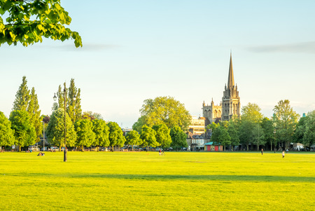 unrecognized: Parkers piece is large park in Cambridge, England, under blue evening sky, with unrecognized people