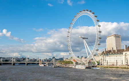 LONDON - MAY 24: London Eye, the giant ferris wheel at the South bank of River Thames in London, England, under cloudy blue sky on May 24, 2016. Editorial