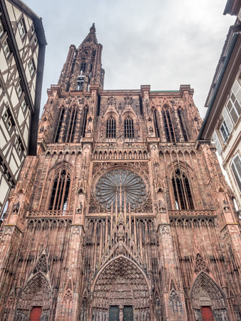 Huge tower and elegant exterior architecture of Notre dam of Strasbourg cathedral in Strasbourg, France, under cloudy sky