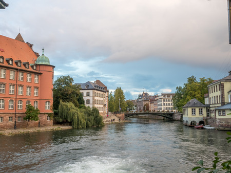 unrecognized: The quarters weirs and half-timbered buildings with unrecognized tourists in Petite France area in Strasbourg, France Stock Photo
