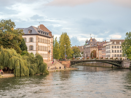 The quarters weirs and half-timbered buildings with unrecognized tourists in Petite France area in Strasbourg, France Editorial