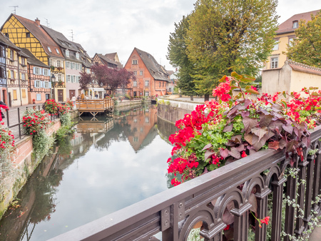COLMAR - OCTOBER 9: Unique peaceful town and buildings in Colmar, known as little Venice, with colorful flowers along canal under cloudy sky in France, on October 9, 2016. Editorial