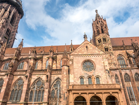 Corridor and sculpture of Mother Mary of Freiburg minster cathedral under cloudy sky in Black forest, Germany Stock Photo