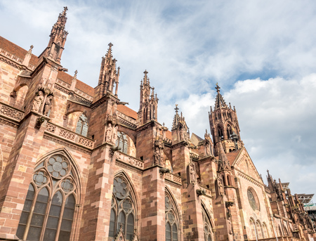 freiburg: Corridor and sculpture of Mother Mary of Freiburg minster cathedral under cloudy sky in Black forest, Germany Stock Photo