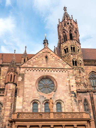 freiburg: Tall clock tower of Freiburg minster cathedral of our lady under cloudy sky in Freiburg, Germany Stock Photo