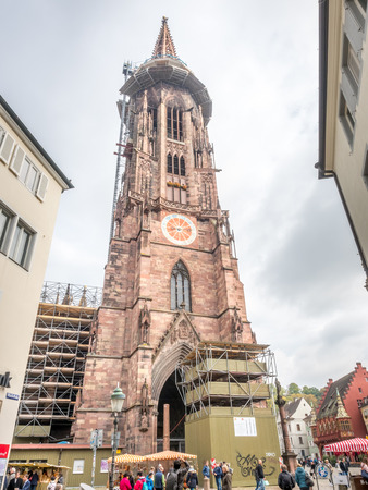 freiburg: Tall clock tower of Freiburg minster cathedral of our lady under cloudy sky in Freiburg, Germany Editorial