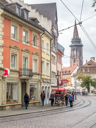 freiburg: FREIBURG - OCTOBER 10 : Freiburg buildings and people with road and transportation (vehicle and tram track) under cloudy sky in Freiburg, Germany, on October 10, 2016. Editorial