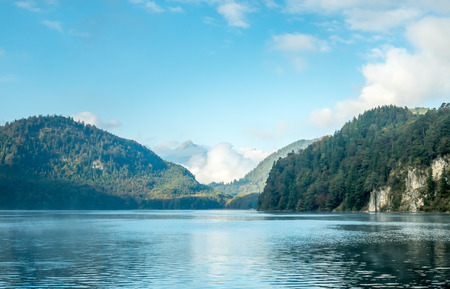 Lake Alpsee, near Hohenschwangau castle, in Bavaria state, with surrounding nature landscape and mountains, Germany, under cloudy blue sky