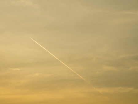 contrail: Aircraft contrail with golden twilight sky background Stock Photo