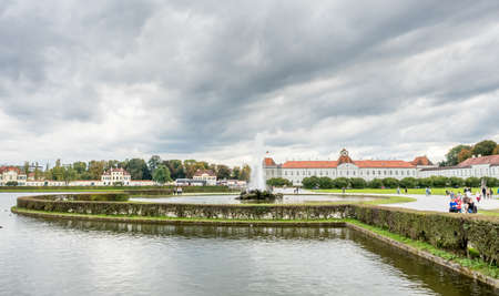 Front view of buildngs of Nymphenburg palace near center of Munich in Germany, under cloudy sky, with unrecognized tourists Editorial