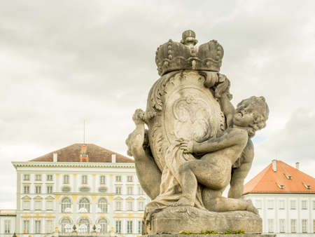 Sculpture at front of buildngs of Nymphenburg palace near center of Munich in Germany, under cloudy sky