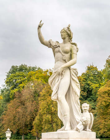 God or angel sculpture in outdoor garden of Nymphenburg palace under cloudy sky in Munich, Germany, with unrecognized tourists Editorial