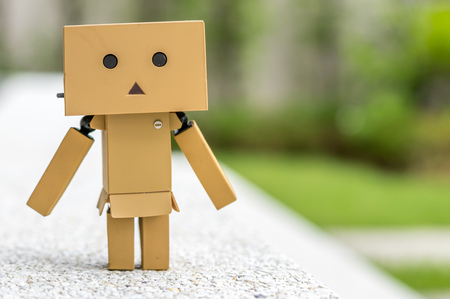 Polite stand action of cute box doll standing at outdoor park with natural light, selective focus at its eye Stock Photo