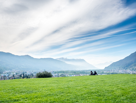 Two unrecognized people sit together on green grass with Bellinzona cityscape view and surrounding mountains in Switzerland, under cloudy blue sky