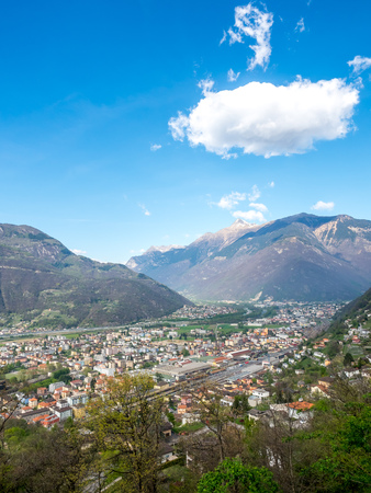 Bellinzona cityscape view from castle under cloudy blue sky in Switzerland, surrounding with high Alps mountains Editorial