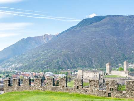 Bellinzona cityscape view with old rock castle wall under cloudy blue sky in Switzerland, surrounding with high Alps mountains Editorial