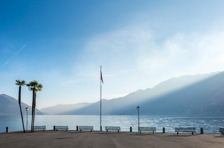 Scène extérieure vue côté du lac Majeur avec banc, palmier et drapeau à Locarno, Suisse Banque d'images