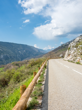 Road in the mountains near Gr�oli�res village in France, under cloudy blue sky