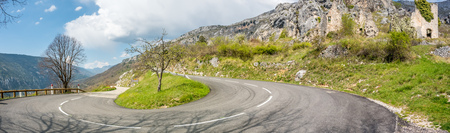 commune: Panoramic view of road in the mountains near Gréolières village in France, under cloudy blue sky