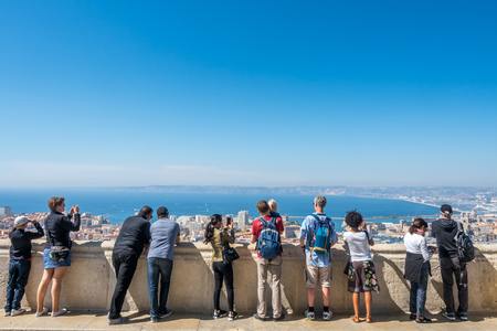 MARSEILLE - APRIL 11 : Tourists at corridor of Basilica of Our Lady of the Guard (Notre-Dame de la Guard) catholic church look cityscape viewpoint of Marseille, France, on April 11, 2017.