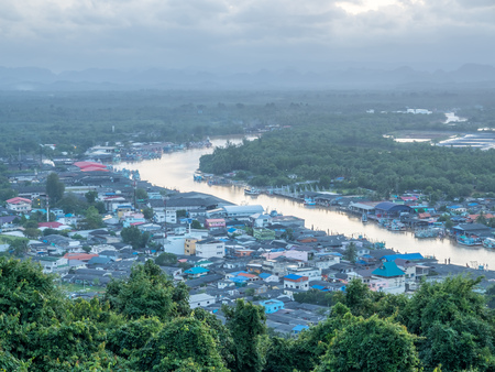 brackish water: River and cityscape view of fisherman village under twilight evening sunlight from highland viewpoint in Chumphon estuary town, Thailand Stock Photo