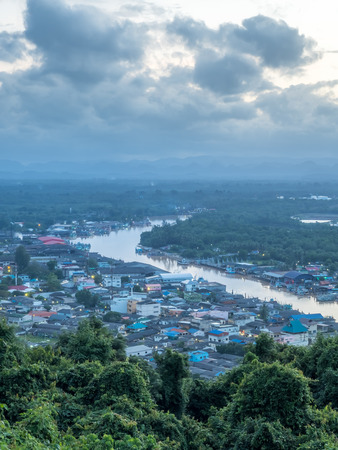 River and cityscape view of fisherman village under twilight evening sunlight from highland viewpoint in Chumphon estuary town, Thailand Stock Photo