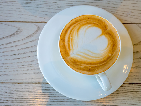 Coffee with milk, known as Latte or cafe au lait, in white cup drink with breakfast in morning time