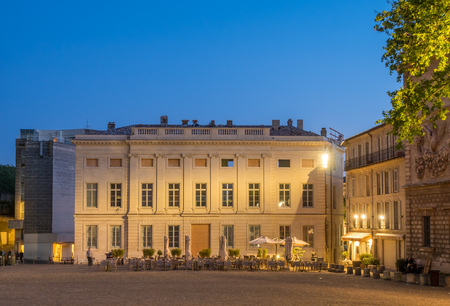 Scene around Papal Palace square in Avignon, France, under twilight evening sky