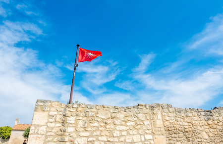 LES BAUX-DE-PROVENCE - APRIL 12 : Flag sign on stone wall of Castle of Les Baux-de-provence, France, under cloudy blue sky, on April 12, 2017.