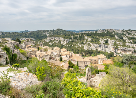 Lower courtyards of area around Chateau des Baux-de-provence in france with unrecognized tourists, under cloudy blue sky Stok Fotoğraf