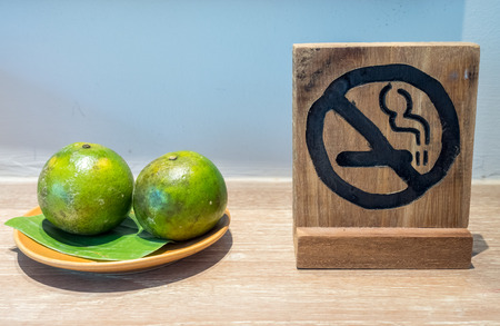 No smoking sign with complimentary green orange fruits on wooden table