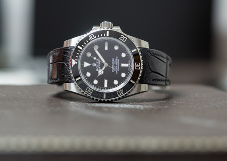 BANGKOK - SEPTEMBER 24 : Rolex submariner no date model with ceramic bezel, the most popular luxury watch, and alligator leather strap on leather surface table, was taken on September 24, 2017, in Bangkok, Thailand