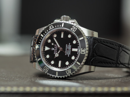 BANGKOK - SEPTEMBER 24 : Rolex submariner no date model with ceramic bezel, the most popular luxury watch, and alligator leather strap on leather surface table, was taken on September 24, 2017, in Bangkok, Thailand Stock Photo - 86655938