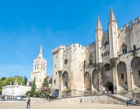 Avignon cathedral (Cathedral of Our Lady of Doms) next to Papal palace (Palais des Papes)  under clear blue sky in Avignon, France Editorial