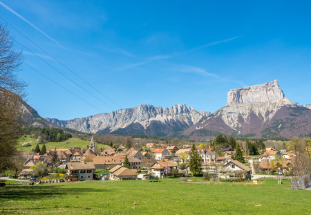 Buildings of house in Chichilianne town, small town in valley, countryside of France, under clear blue sky in spring season, with mount Aiguille in background