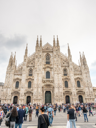 MILAN, ITALY - APRIL 15 : Exterior architecture of Milan Cathedral, known as Duomo di Milano, the largest church in Italy, with crowded tourists, on April 15, 2017.