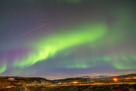Aurora Borealis, known as Northern lights, is amazing green color light over night sky in high lattitude region, natural phenomenon in Iceland
