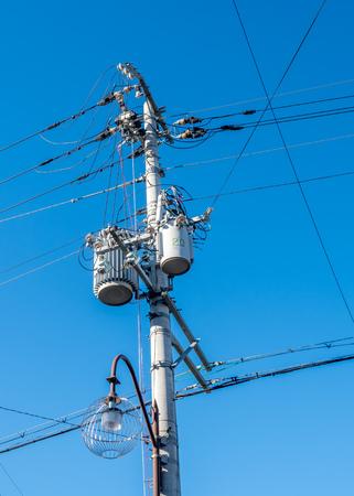 Electricity pole with light lantern under blue sky Фото со стока - 99630807