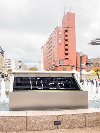 KANAZAWA, JAPAN - NOVEMBER 25 : Outdoor fountain clock at front side of Kanazawa train station with surrounding buildings in Kanazawa, Japan, on November 25, 2017.
