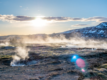 The Great geysir, periodically spouting hot spring, natural phenomenon and one of landmark in Iceland, with lens flaring effect