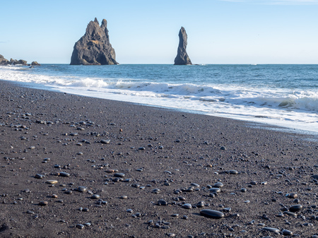 Reynisfjara black sand beach is landmark of Vik town in Iceland, fine black sand with small stones on beach with mountain and islands in background, under blue sky in winter season