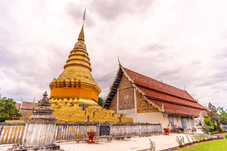 Golden pagoda with old classic northern art style pavilion in Nan city, Thailand, under cloud sky