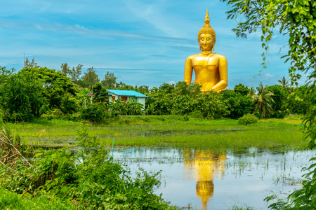 Huge golden lord Buddha sculpture located in outdoor in Wat Muang in Angthong province, Thailand, under blue sky