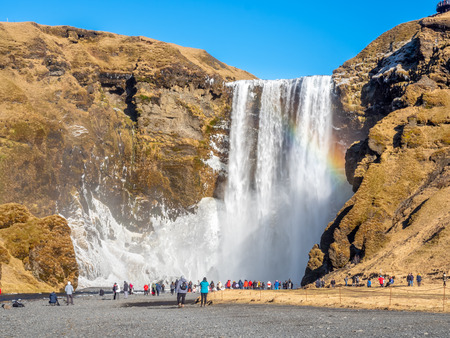 Skogafoss, large waterfall landmark in Iceland, with rainbow refraction, in winter season, with snow and ice Stok Fotoğraf
