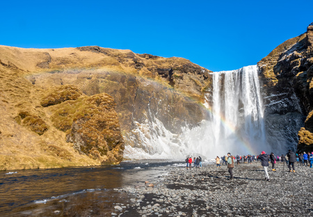 ICELAND - MARCH 3 : Skogafoss waterfall with rainbow refraction, with snow and ice in winter season and crowded with tourists in Iceland, on March 3, 2018. Editöryel