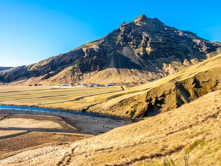 Mountains, hills, meadow and field near Skogafoss waterfall in winter season in Iceland